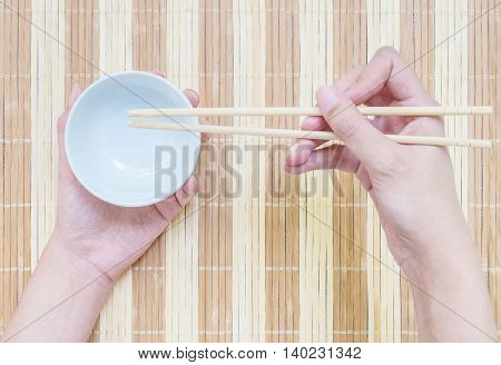 Closeup white ceramic chalice with blurred wood chopsticks in woman hand on wood mat textured background on dining table in top view in eating concept