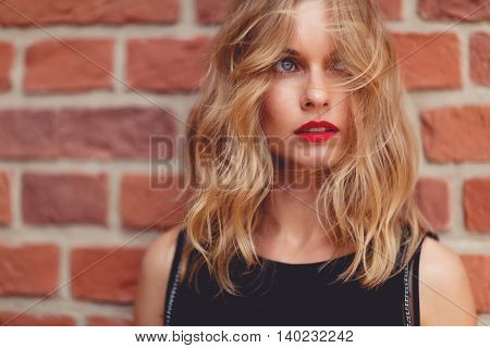 Closeup portrait of beautiful caucasian woman standing behind brick wall outside and looking away. Shoot on fast aperture