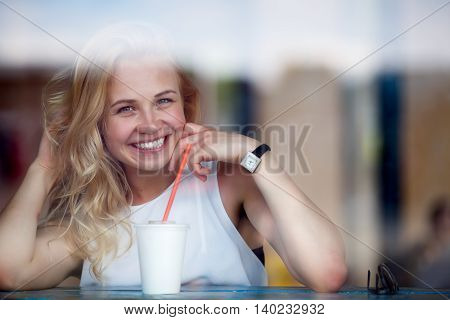 Cheerful blonde woman with milkshake sitting in cafe and looking at camera