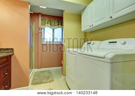 Laundry Area In Bathroom With White Appliances.