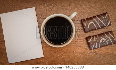 Blank paper and black coffee cup on wood table