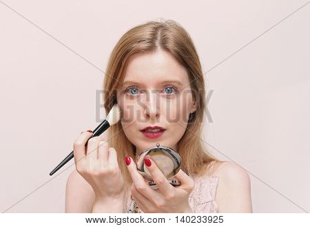 Beautiful blue eyed woman putting blush make up with mirror in hand