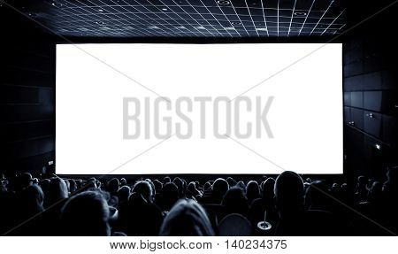 Cinema. The audience in 3D glasses watching a movie. A white screen for your image.