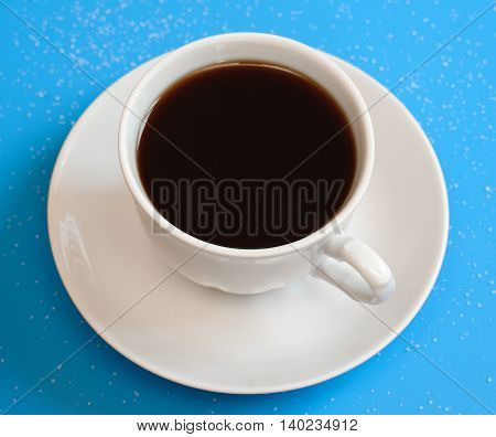 Coffee cup and saucer on a blue background.