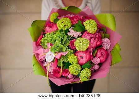 girl holding a bouquet of pink and green flowers