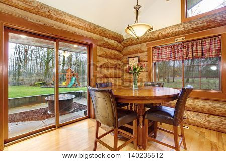 Dining Table With Leather Chairs In Log Cabin House.