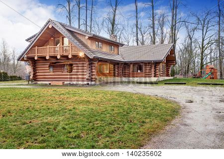 Large Log Cabin House Exterior With Kids Playground.