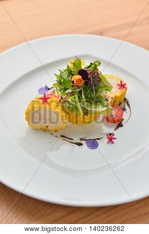 Loin of corn with herbs on white plate in restaurant