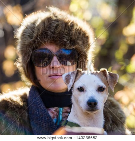 woman with a dog on holiday in the autumn park