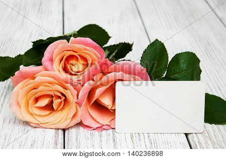Pink roses and greeting card on a old wooden background