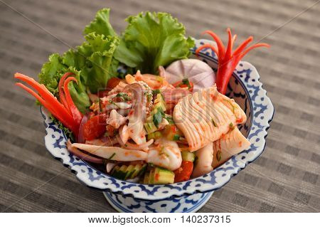 Seafood mix with octopus and herbs in bowl