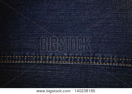 Surface texture of blue jeans textile with yellow thread stitch