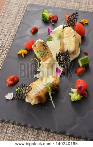 Fried fish with tomato and herbs on black tray