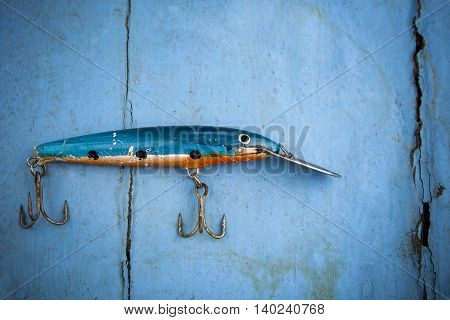 old fishing lure on blue wood background