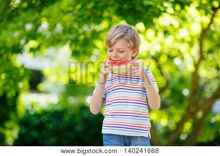 Adorable little preschool kid boy with blond hairs eating watermelon in summer garden. Funny happy child smiling and tasting healthy fruit snack on sunny day.