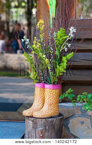Decorative bouquet of flowers in Boots on wooden background.