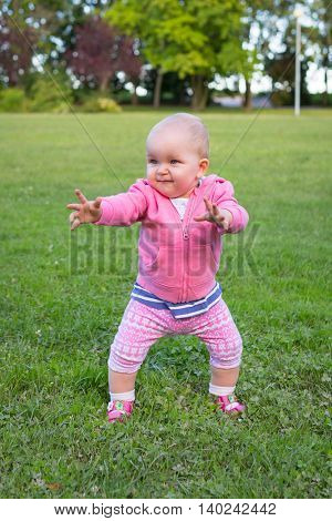 Little baby girl walking in the park