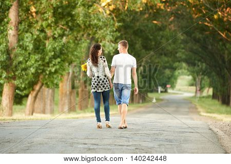 young couple walk on country road an sunset, romantic people concept, summer season