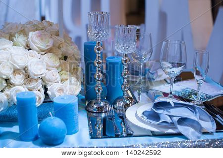 Wedding decor in blue. candles and flowers on the table.