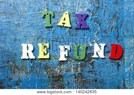 tax refund text on colorful wooden letters. Wood abc at blue grunge background.