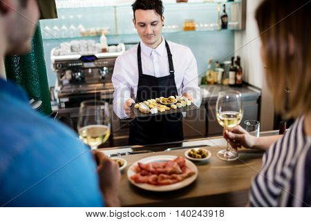 Young bartender serving food to customer at counter in restaurant