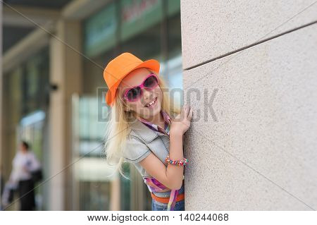 Adorable happy child in sunglasses and orange hat. Shop windows in the background.Adorable happy child in sunglasses and orange hat. Shop windows in the background. Girl peeking around the corner. Blond hair fluttering in the wind.