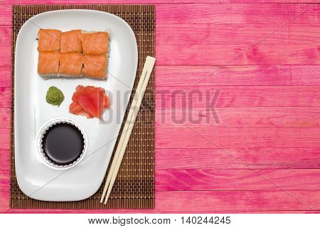 sushi roll set on white plate with wasabi and ginger