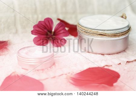 Wonderful cosmetic cream, pink flowers. Herbal skincare. Soft focus on container with twine, natural blur.