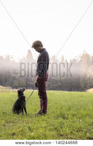 Single adult man in long sleeve shirt standing in front of fog around woods with friendly dog looking at him.