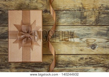 Brown gift box with silk ribbon on old wooden table