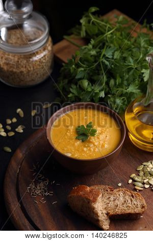Pumpkin cream soup on wooden board. Arranged with bread, green and spices. Healthy, appetizing, delicious, vegetarian food. Top view, copy space.