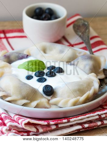 Vareniki. Dumplings With Blueberries. Served With Sour Cream. Dish Of Russian And Ukrainian Cuisine.