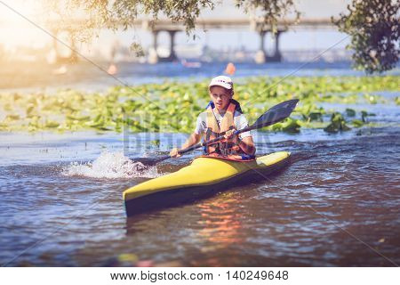 Young lady paddling hard the kayak with lots of splashes