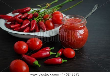 Tomato ketchup sauce with cherry tomatoes and mini red hot chili peppers in a small glass jar with a spoon on dark wooden background. Homemade tomato sauce and fresh tomatoes. Selective focus.
