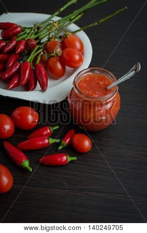 Home made ketchup in a jar. Tomato ketchup sauce with cherry tomatoes and mini red hot chili peppers in a small glass jar with a spoon on dark wooden background. Selective focus. Copy space.