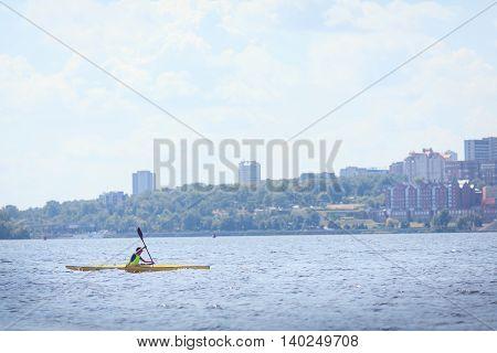 man paddling in kayak is on a river kayaking