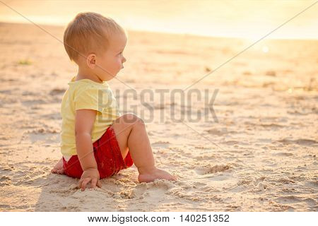 Boy sitting on beach at sunset and looking into sea. Warm color-toning applied