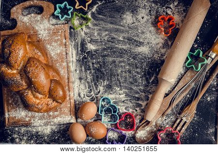 Baking children concept. Baking cookies for kids top view of variety of baking utensils with bread eggs and colorful cutters on black chalkboard. Family fun. Children cooking. Baby art.