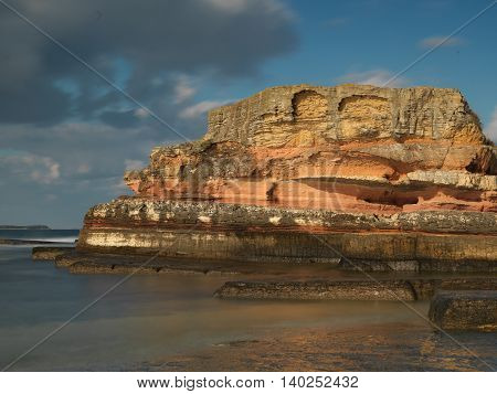 Long exposure shot on amazing pink rocks and sea