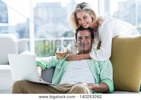 Portrait of mid adult couple using laptop at home