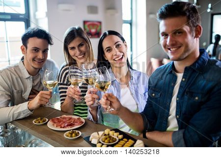 Portrait of happy friends enjoying wine and food at bar counter