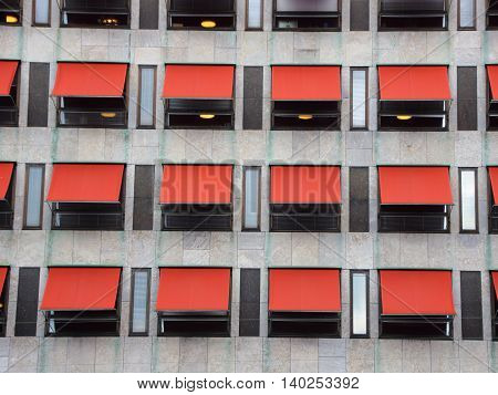 Twelve Red Overhang Sunshades on Modern Building Facade Protecting from the Sun
