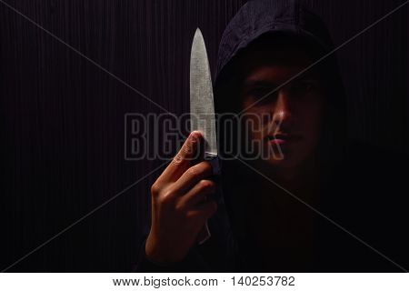 Closeup Portrait Of A Young Man In A Hoodie, Holding A Knife In His Hand, About To Attack, Over Blac
