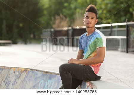 Young african man sitting down in a skate park while enjying the time.