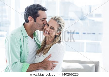 Mid adult romantic man kissing woman at home