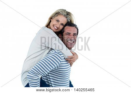 Portrait of happy man carrying woman piggyback against white background