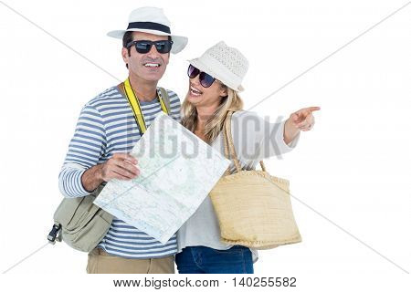 Happy mid adult couple pointing while holding map against white background