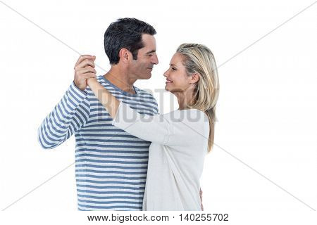 Mid adult romantic couple dancing against white background
