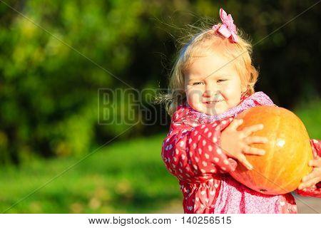 little girl holding pumpkin in autumn garden, autumn harvest