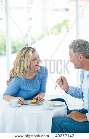 Smiling mature couple discussing while having food at restaurant